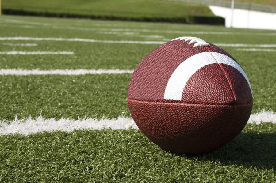 Closeup of American football on field with yard lines.